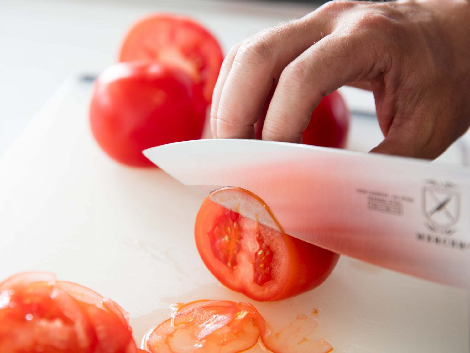 A chef's knife slicing through ripe tomatoes