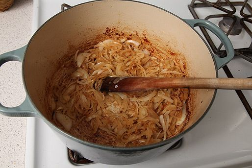 Onions caramelizing in the bottom of an enamel cast iron Dutch oven.