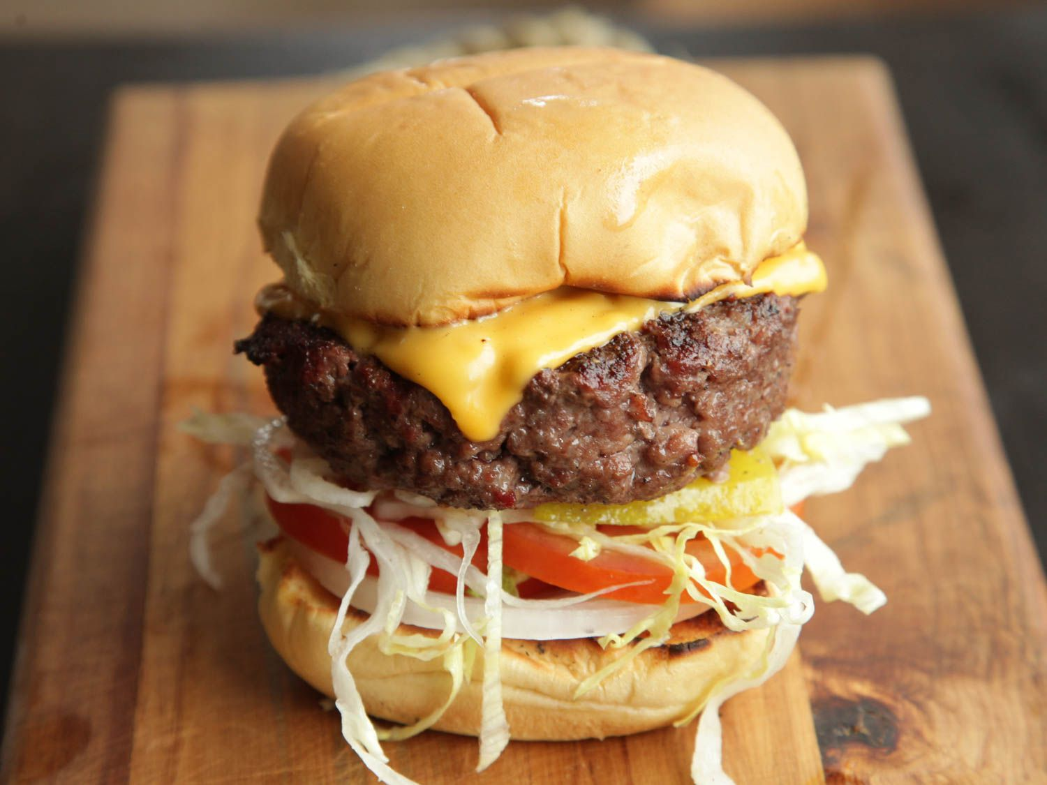 A thick grilled cheeseburger on a bun with shredded lettuce, onion, and tomato