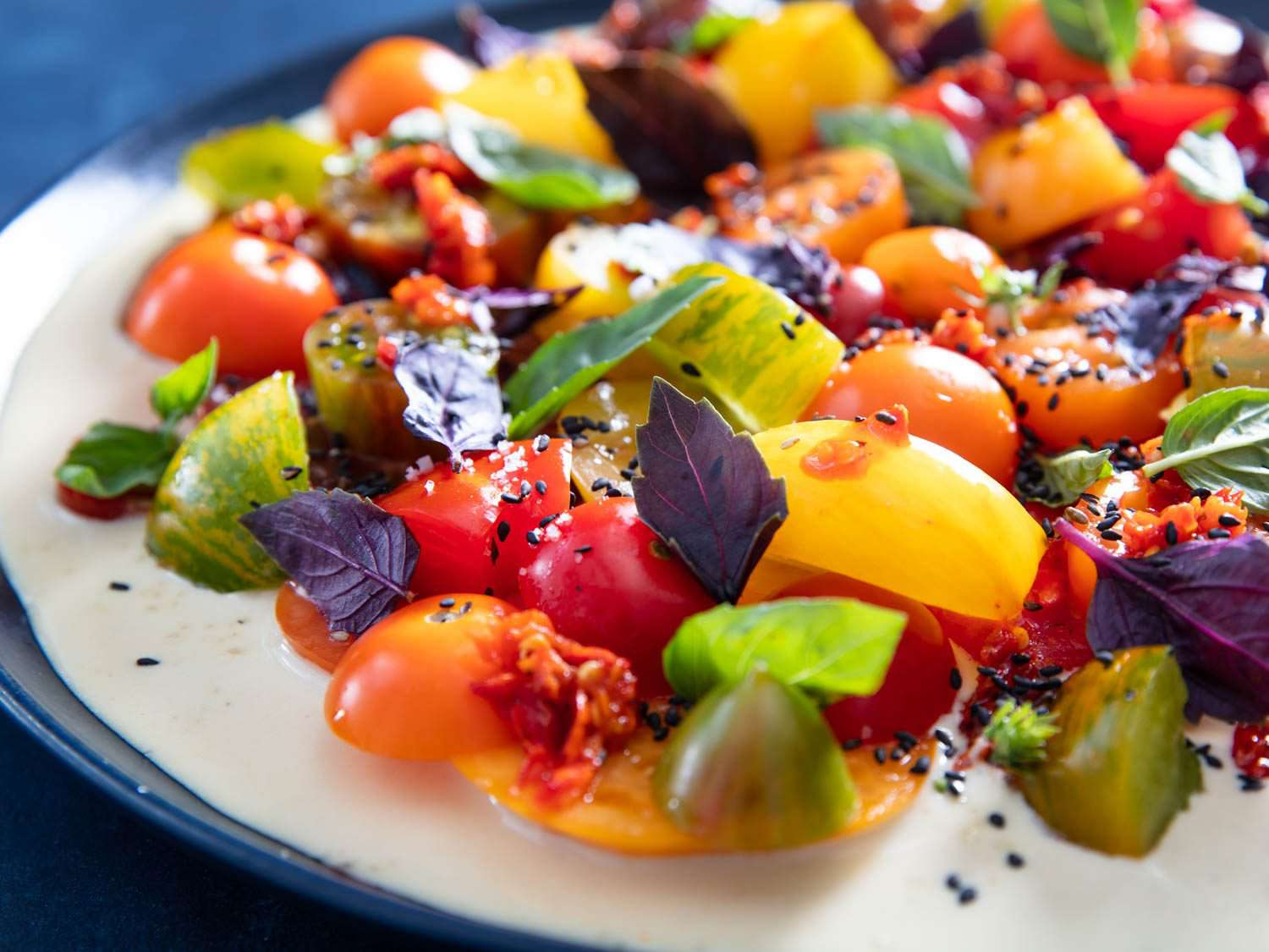 Closeup side view of tomato salad with tonnato sauce, green and purple basil, Calabrian chilies, and black sesame seeds.
