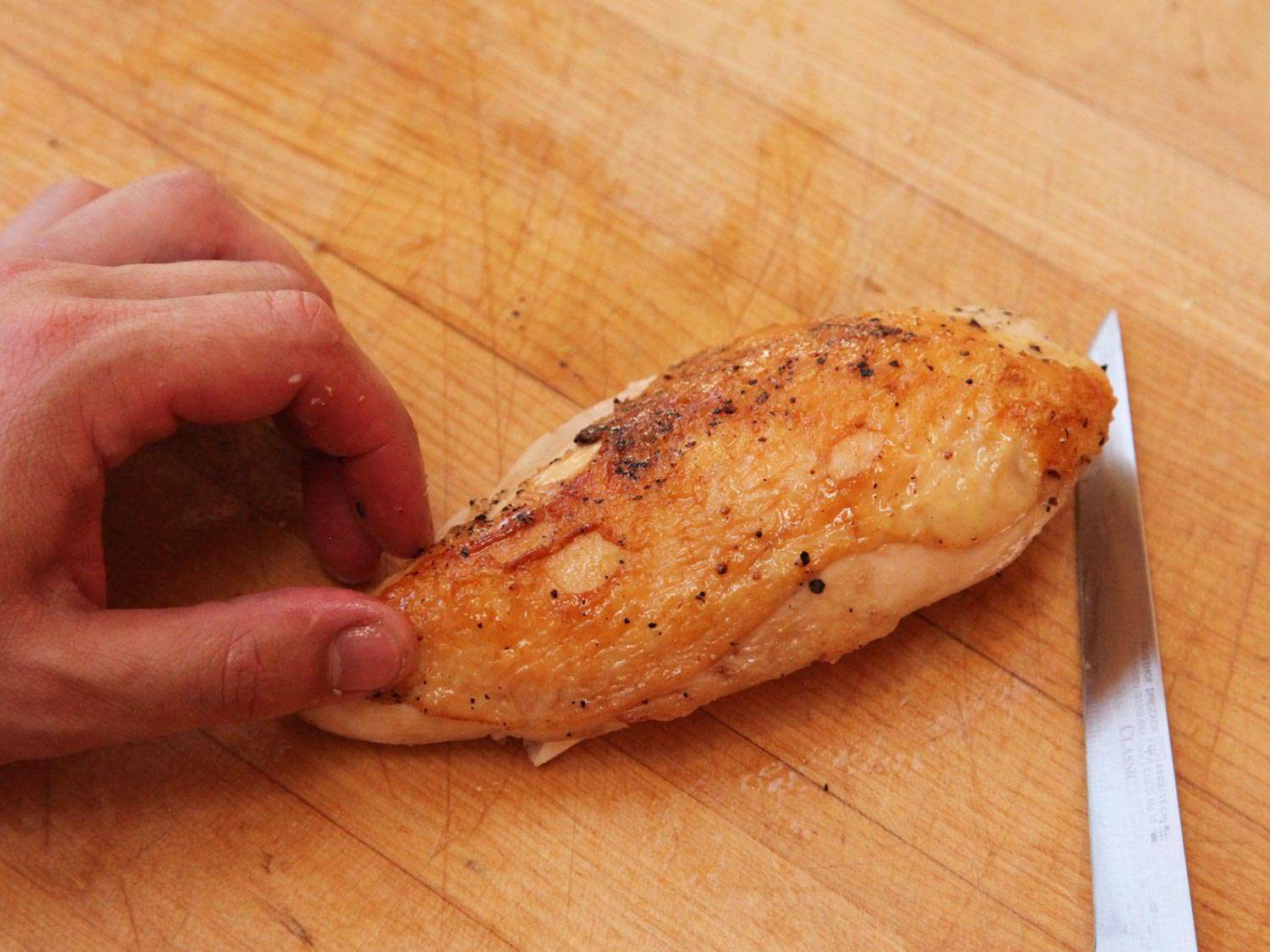 A chicken breast, cooked sous vide and finished on the stovetop, on a wooden cutting board next to a knife