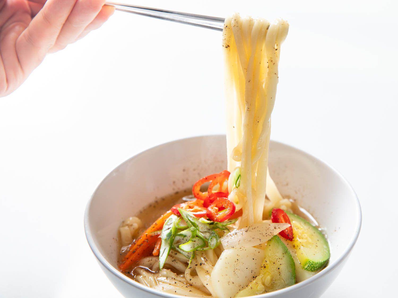 A pair of chopsticks lifts knife-cut noodles from a bowl of Korean knife-cut noodle soup