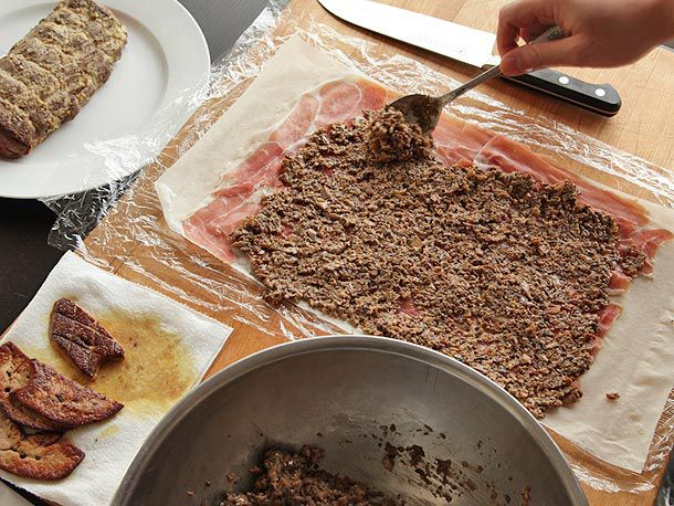 Spreading duxelles on prosciutto and phyllo dough to make beef Wellington.