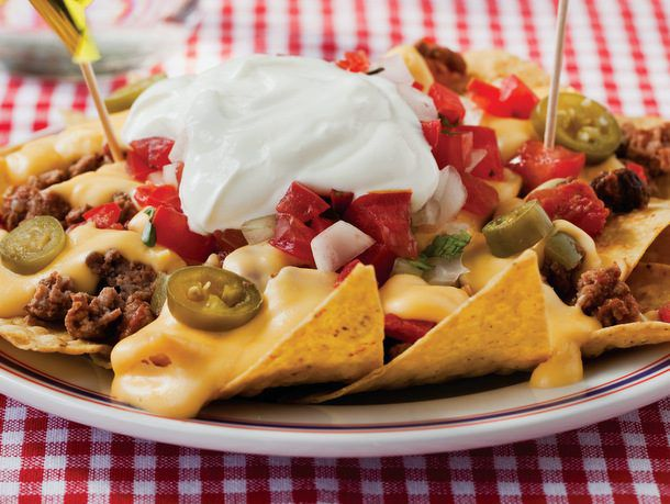 Homemade ball park nachos on a plate with sour cream on top.