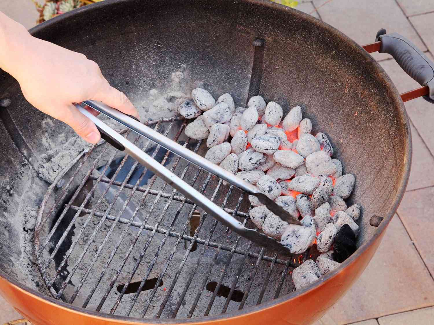 Arranging lit coals on one side of a grill grate for a two-zone fire