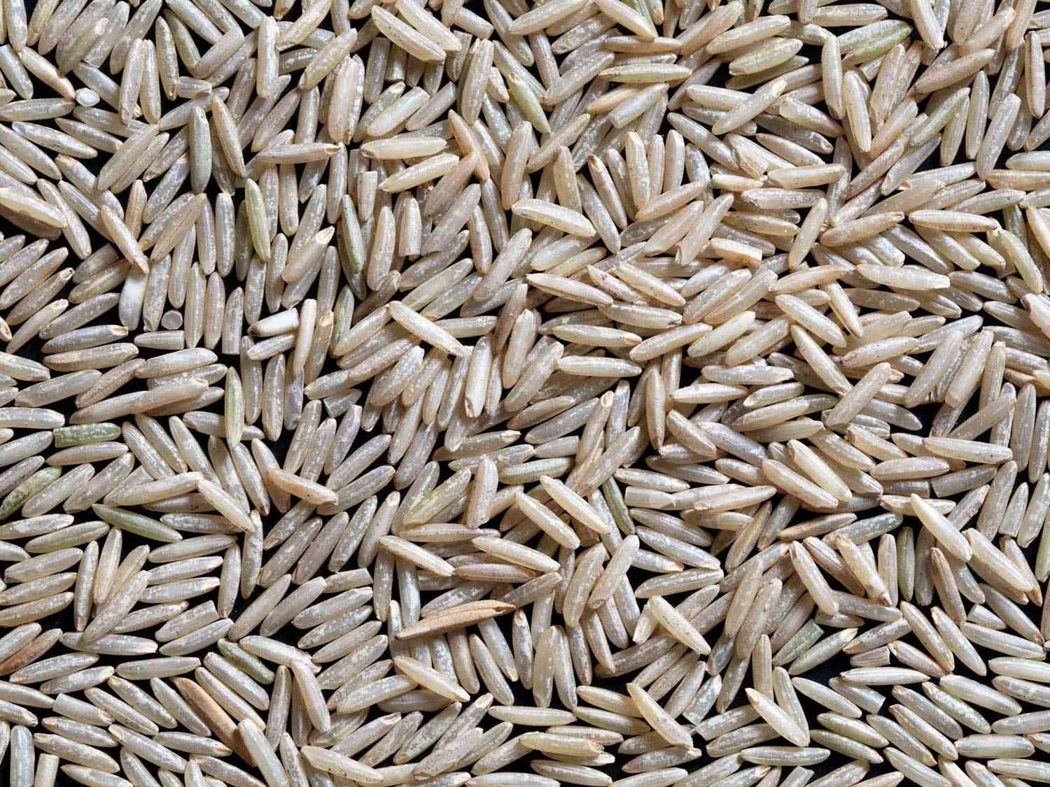 Overhead close-up of long brown basmati rice grains on a flat surface