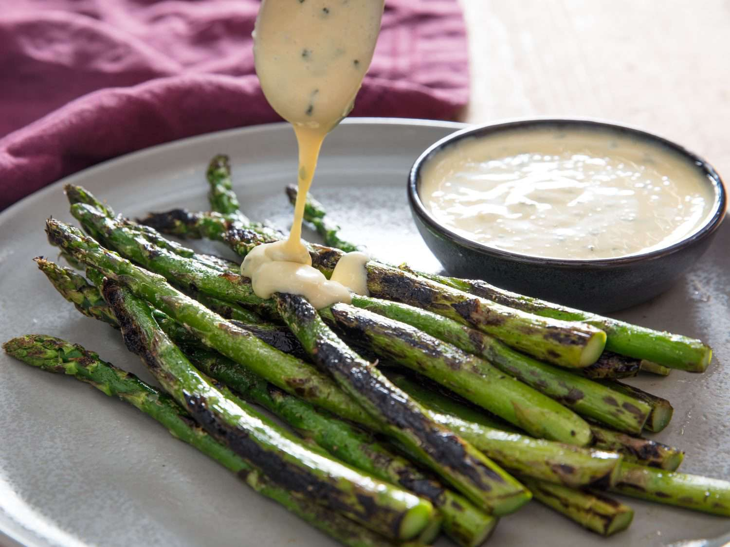 Drizzling miso béarnaise over asparagus.