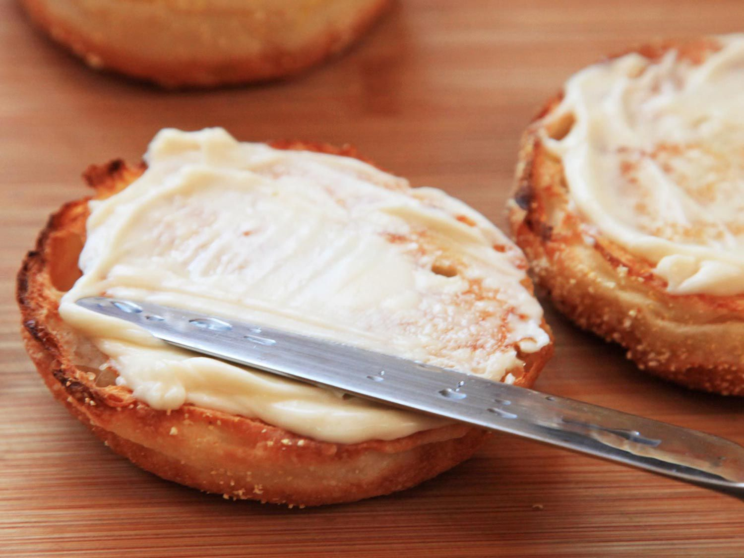 A butter knife spreading mayo on a toasted English muffin