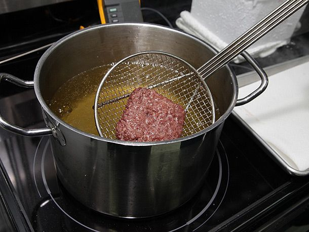 burger patty taken out of hot oil