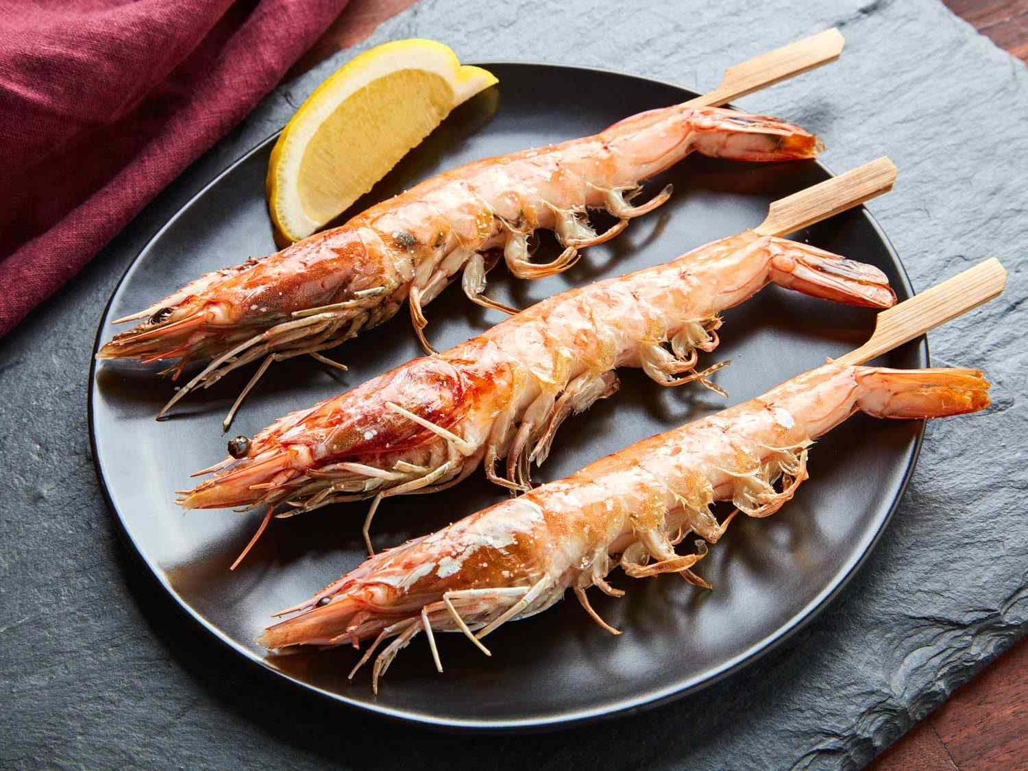 Three cooked head-on shrimp on a plate, with a lemon wedge
