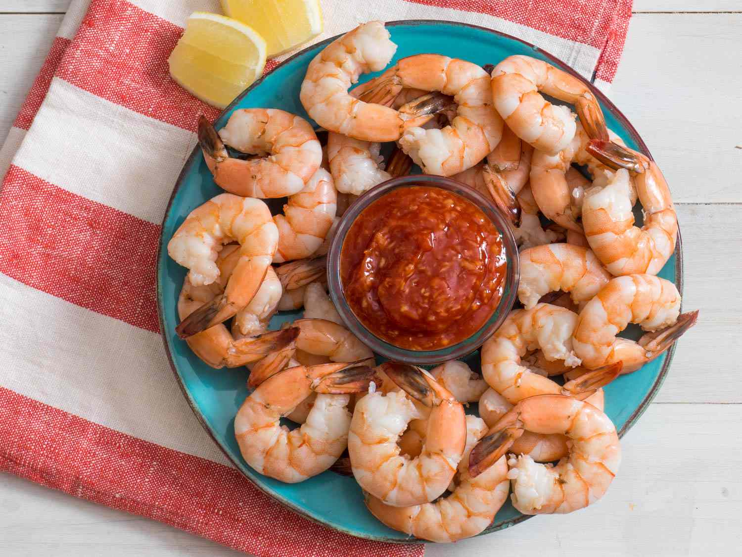 Shrimp cocktail and sauce on a plate with lemon wedges