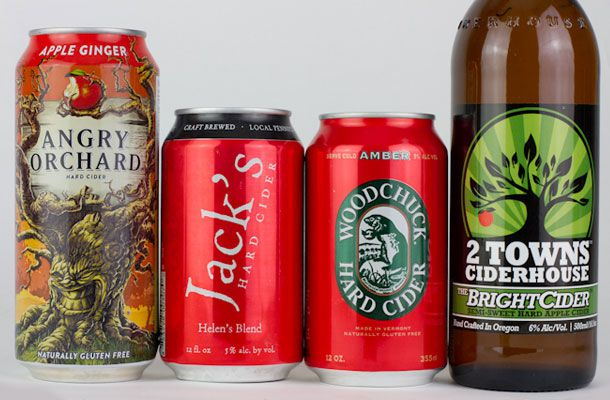 Cans and bottles of Angry Orchard, Jack's Hard Cider, Woodchuck Hard Cider, and 2 Towns Cider House in front of a white background.