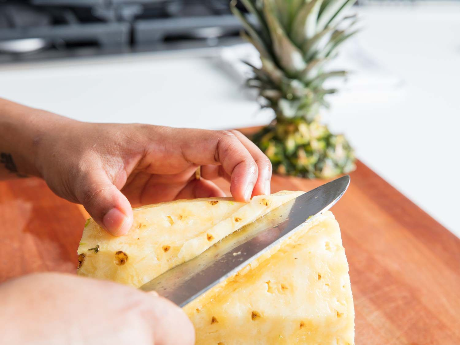 A knife cutting diagonally along the eyes of a pineapple.
