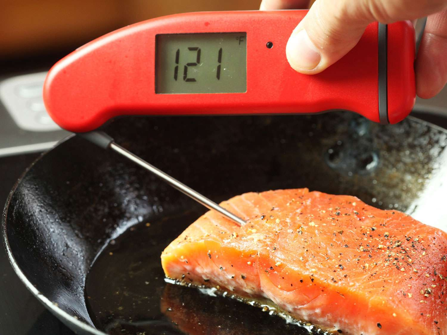 Using an instant read thermometer to see that interior of searing salmon fillet is 121F.