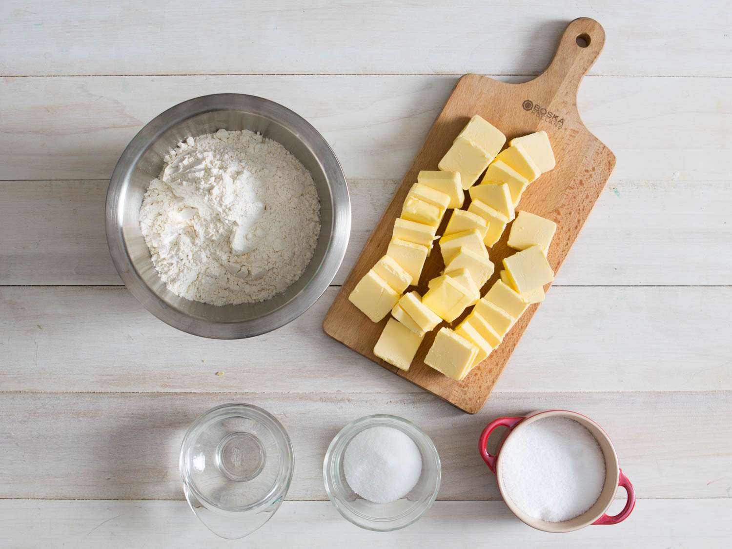 Overhead image showing ingredients (flour, butter, water, sugar, and salt) for all-butter pie dough.