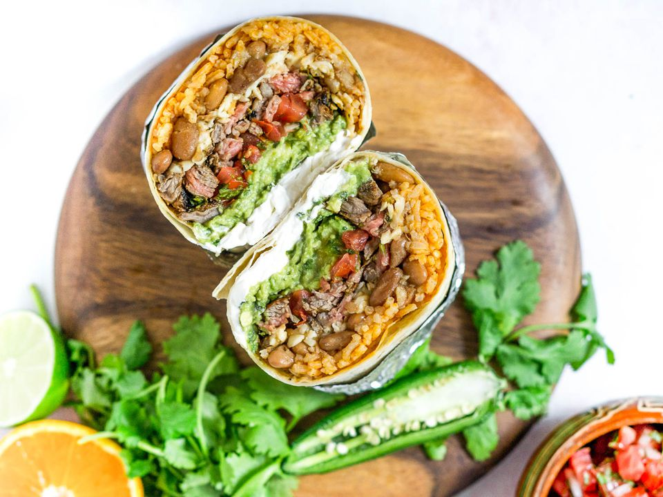A Carne Asada burrito cut in half, exposing the rice, beans, steak, salsa, guacamole and other fillings.