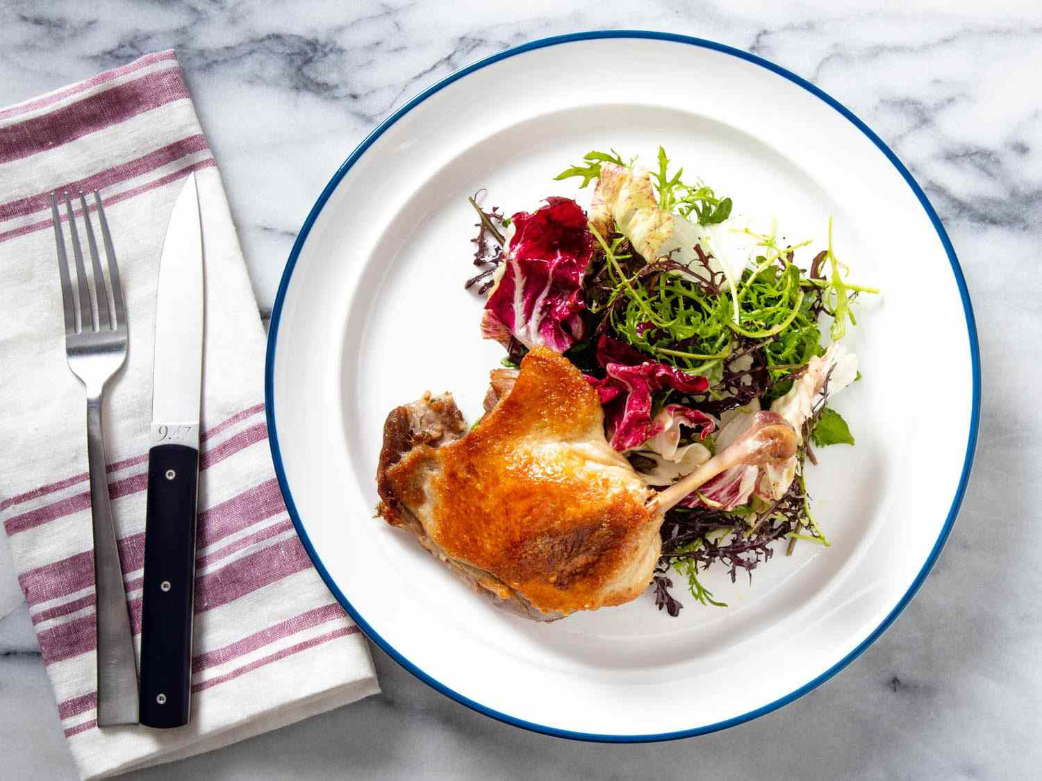 Overhead of a crisped confit duck leg with a mixed greens salad.