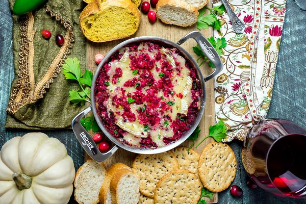 Cranberry Jalapeno Baked Brie on a cutting board with sliced bread and crackers. A glass of red wine is next to the cutting board.