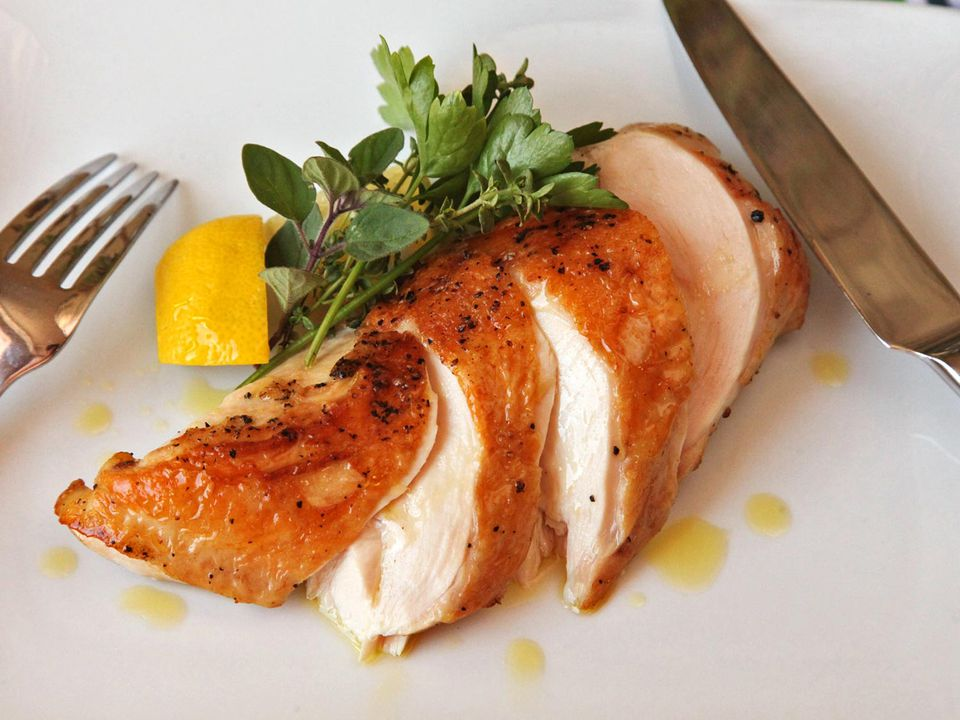 Sliced sous vide chicken breast on a plate, garnished with herbs and lemon