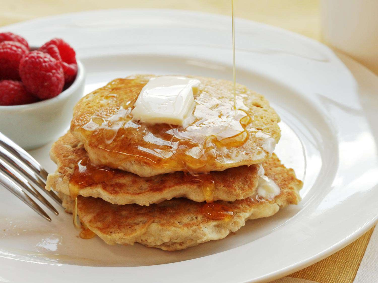 A stack of vegan oatmeal pancakes with syrup and butter. A small dish of raspberries is next to the pancakes.