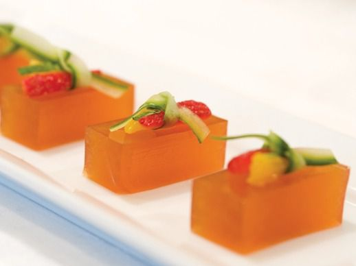 Pimms Cup Jelly Shots cut into rectangular pieces and topped with very small pieces of cucumber and strawberry.