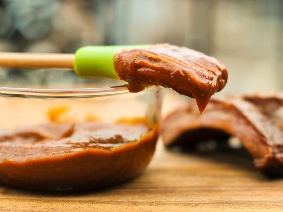 A glass bowl of Kansas City-style barbecue sauce with a basting brush dipped in sauce on top of the bowl. Some cut ribs are in the background.