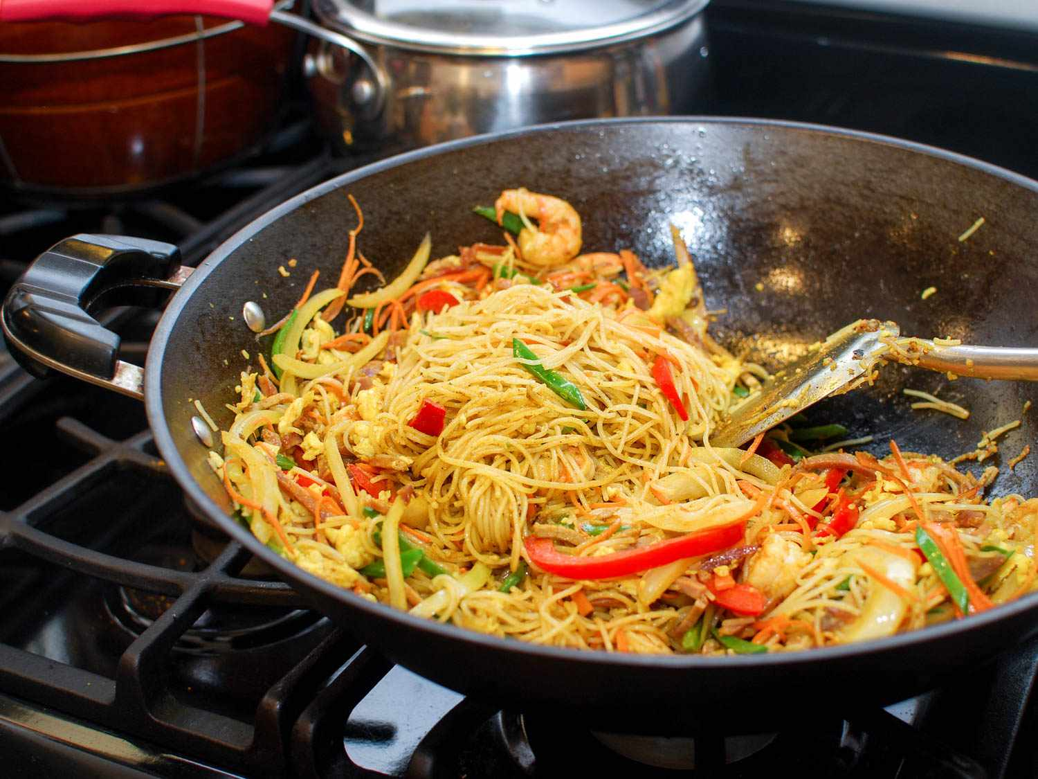 Spatula combining egg, meat, vegetables, and curried vermicelli noodles in a hot wok.
