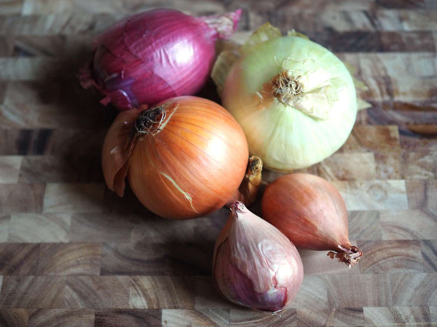 A collection of onions—red, yellow, sweet, and shallots—on a wooden cutting board.