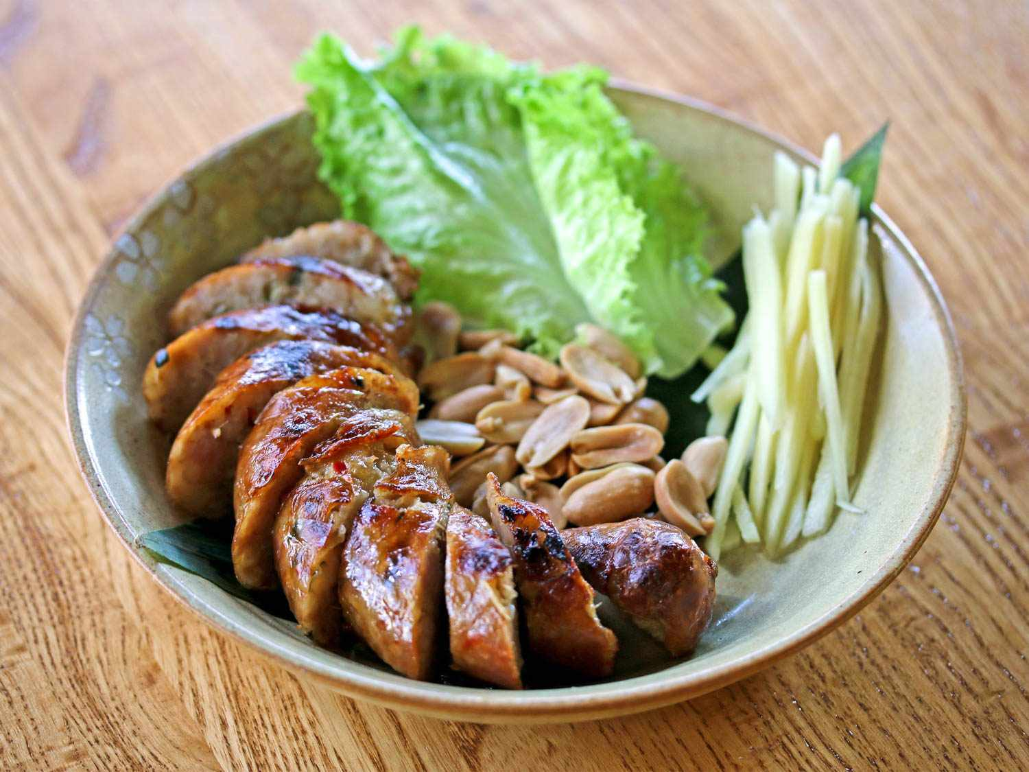 A stoneware bowl with slices of herbed pork sausage (sai oua) and raw vegetables