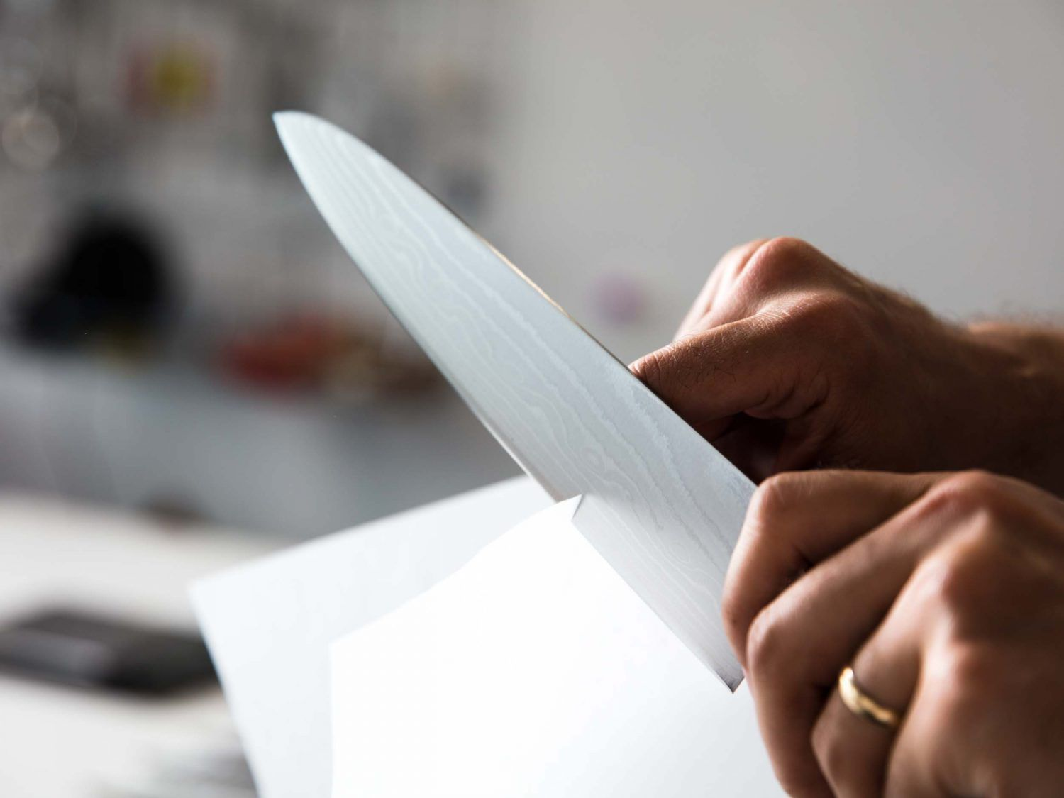 Cutting through paper with the blade of a chef's knife