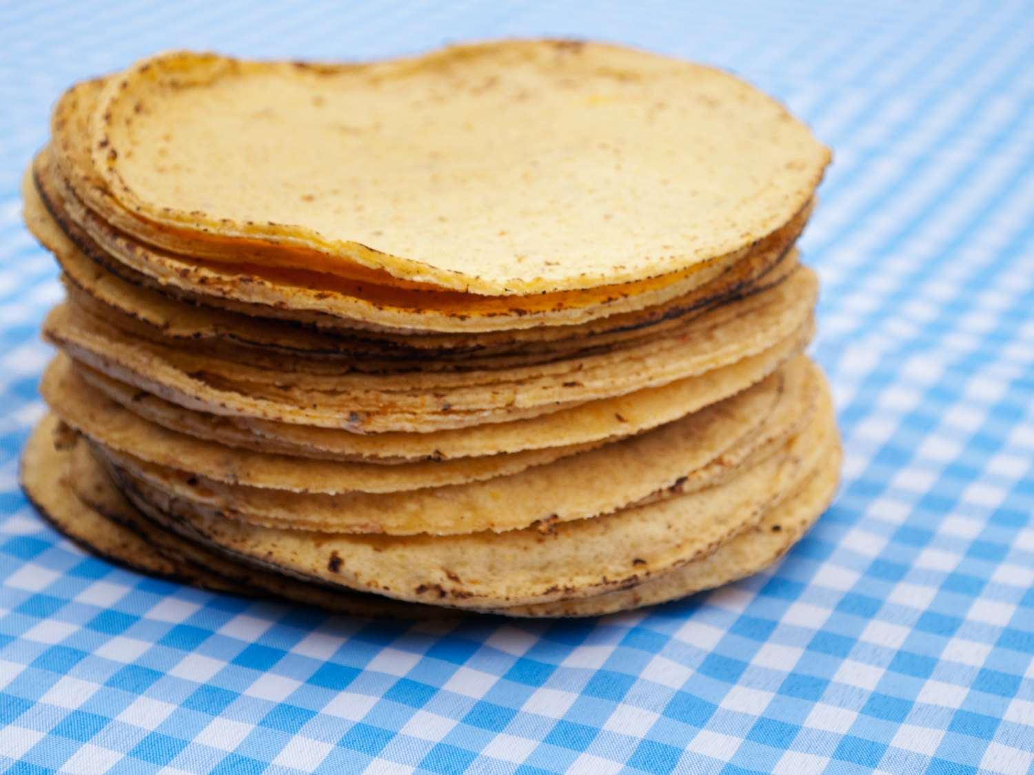 A stack of corn tortillas on a light blue checked tablecloth.