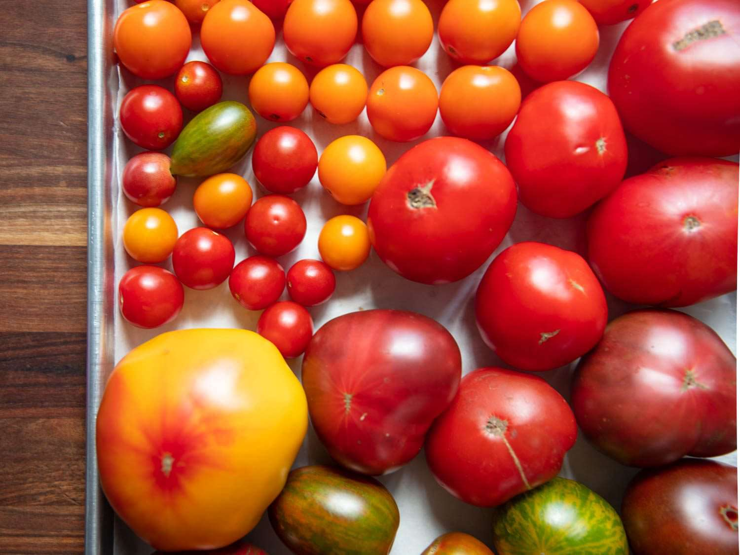 Closeup overhead of a tray of tomatoes of different colors and sizes.