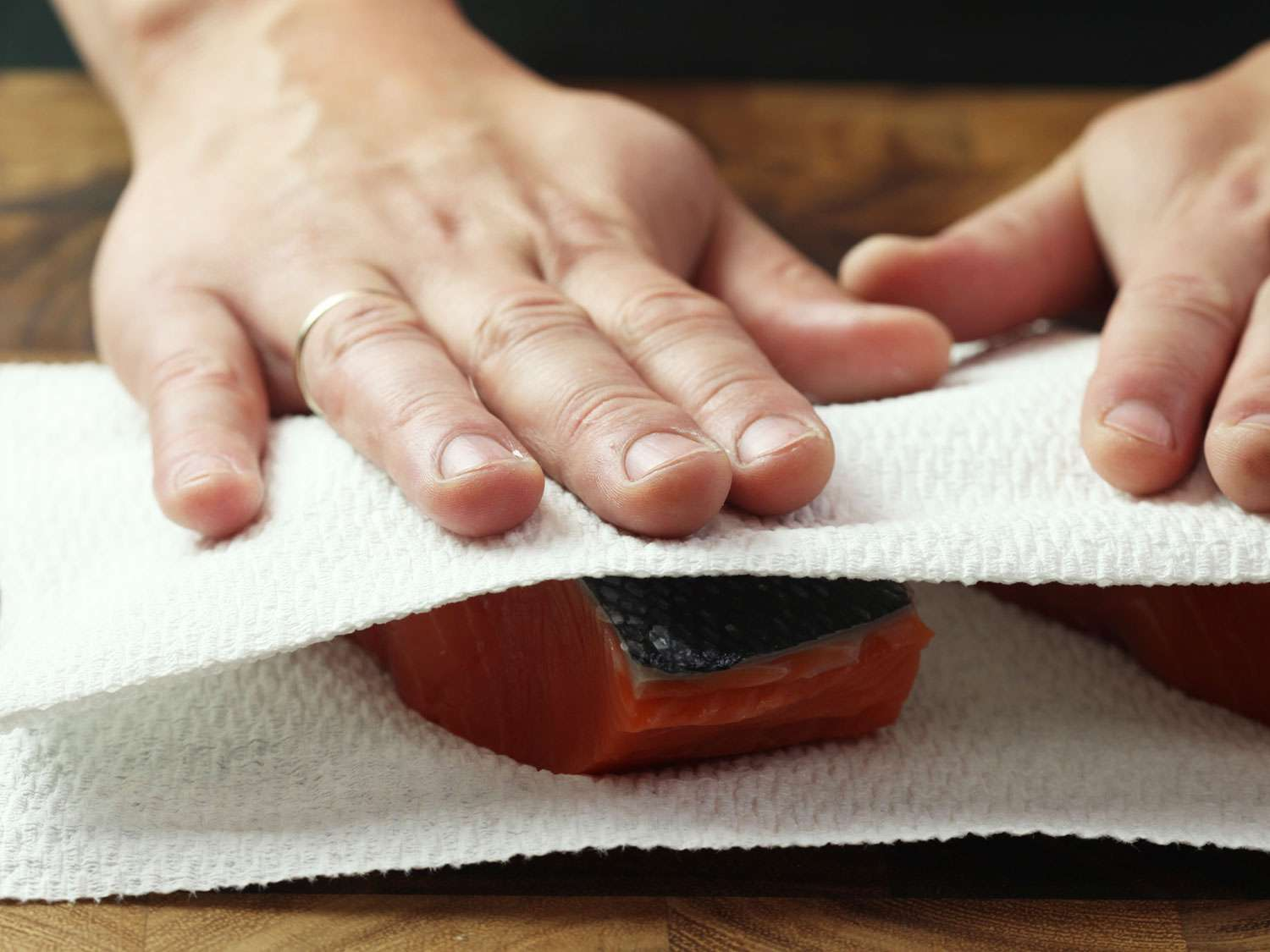 Patting raw, skin-on salmon fillet dry using paper towels on the top and bottom of the fillet.