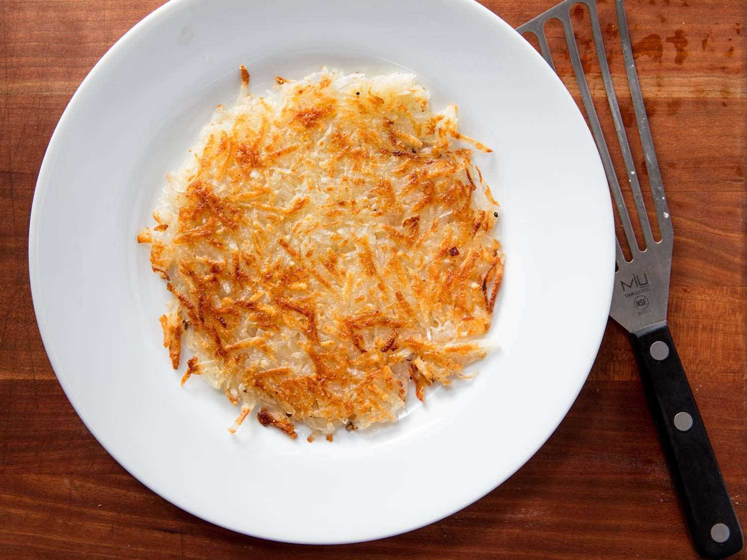 Golden hash browns on a white plate, next to a thin metal fish spatula