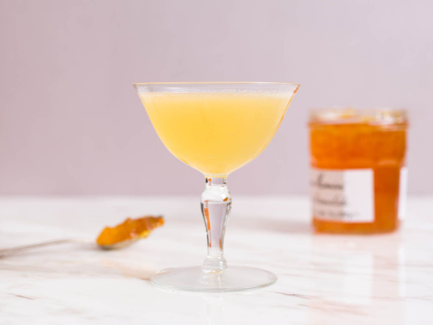A honey and marmalade sour in a cocktail coupe, with a jar of honey behind it.