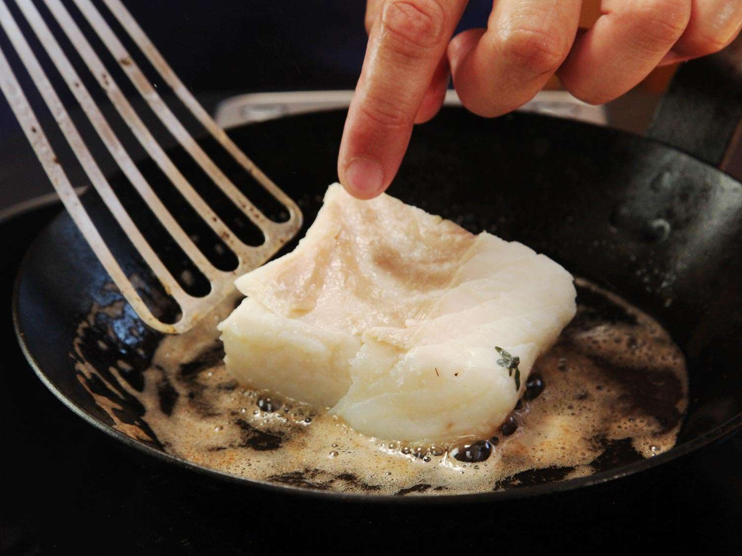 Searing halibut in a carbon steel pan with browned butter.