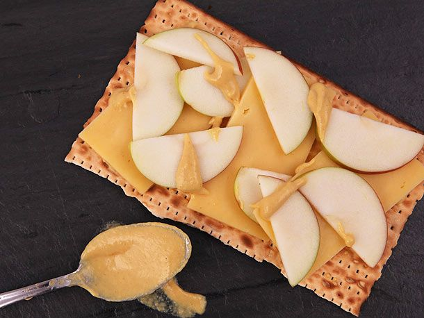 A piece of matzo layered with slices of cheese and apple and dabs of mustard, next to a spoonful of mustard