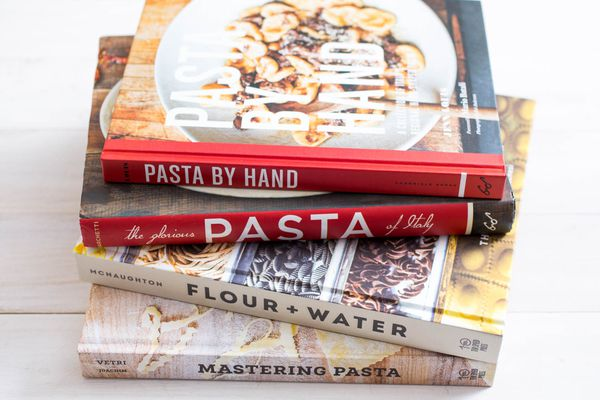 A stack of four cookbooks about pasta.