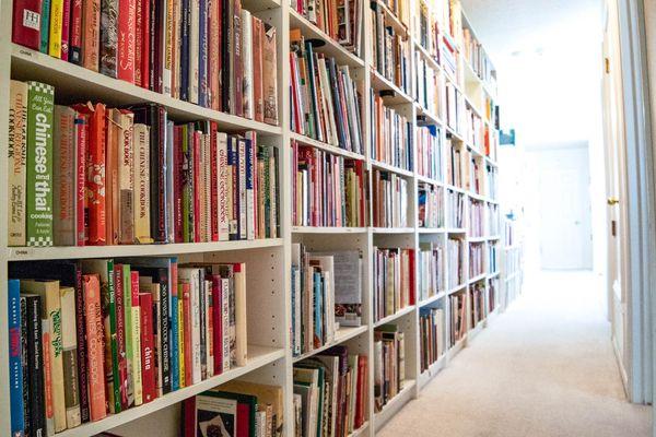 Bookshelves holding hundreds and hundreds of cookbooks.