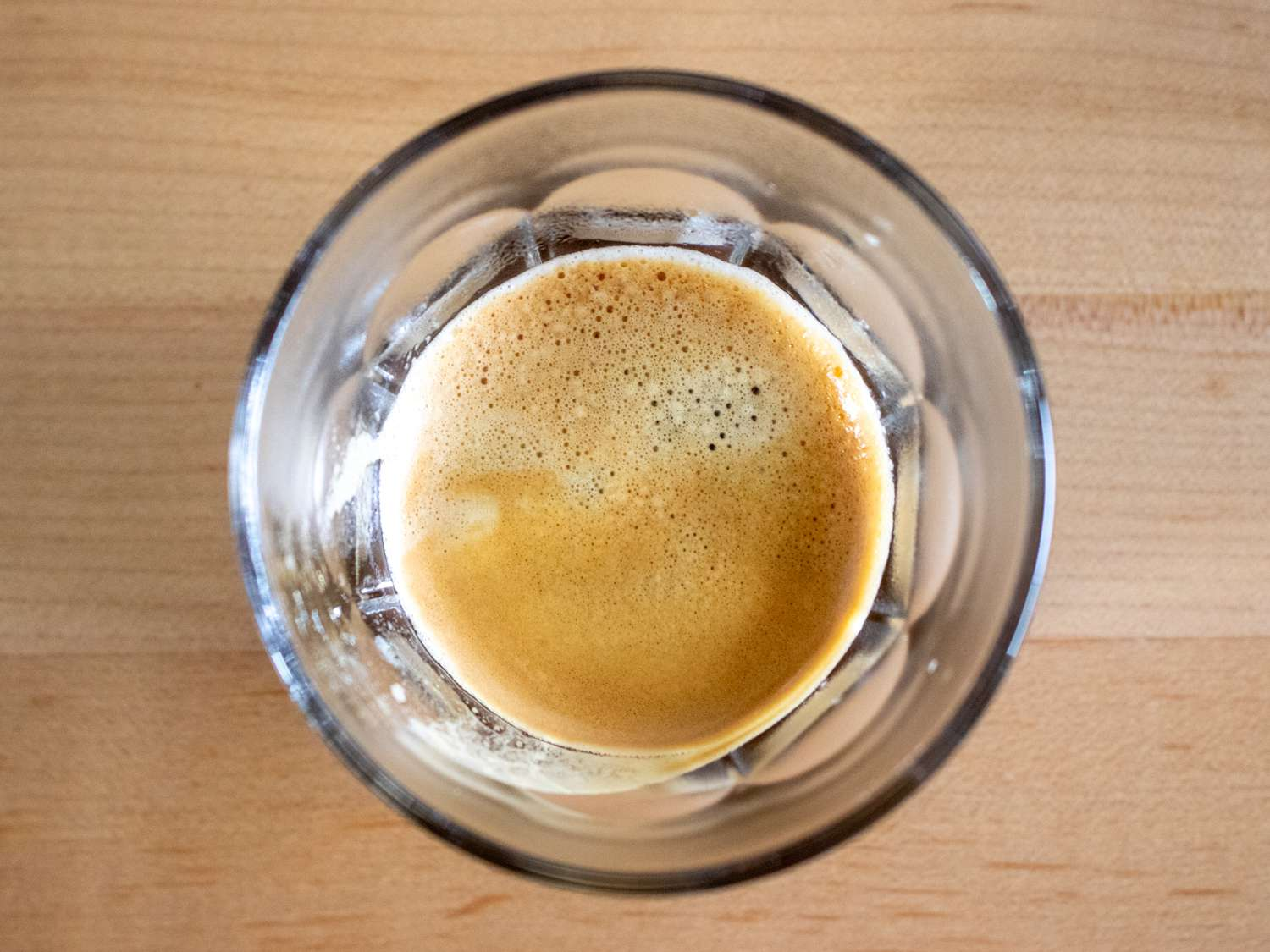 an overhead photo of a shot of espresso in a glass cup