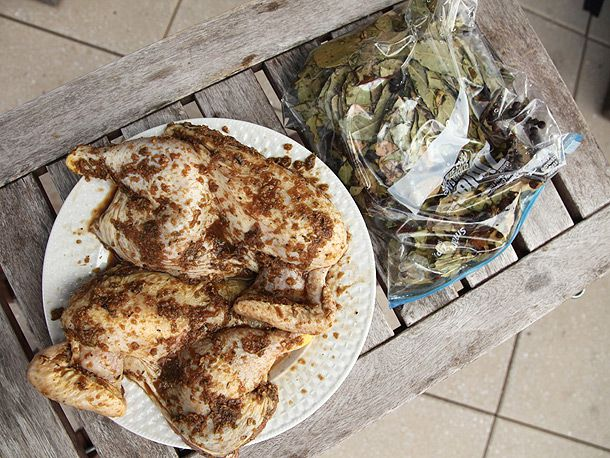 A plate with raw marinated chicken halves, and a bag of bay leaves next to the plate.
