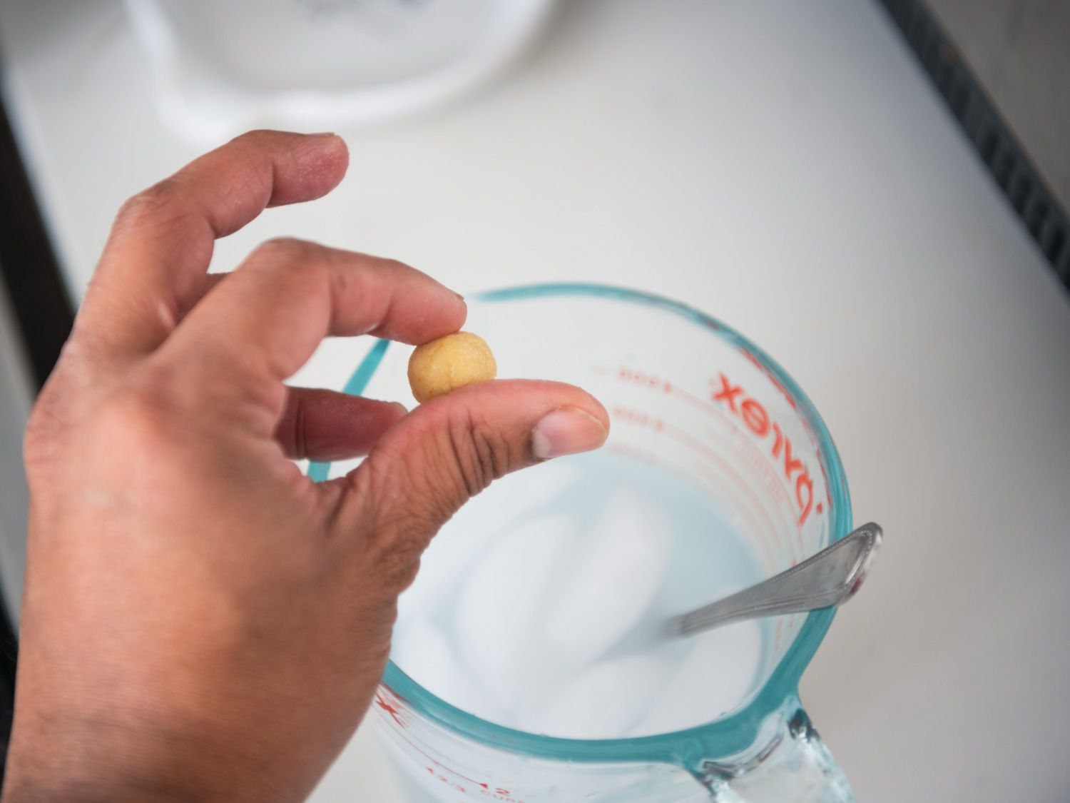 Small piece of milk cream dough formed into a ball between index finger and thumb, after undergoing ice bath test