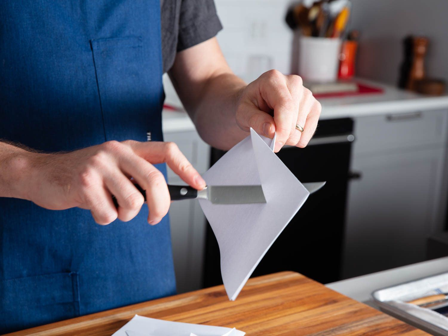 Cutting through a sheet of paper with a steak knife.