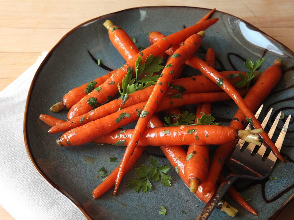 Glazed sous-vide carrots tossed with chopped parsley on a grey plate.