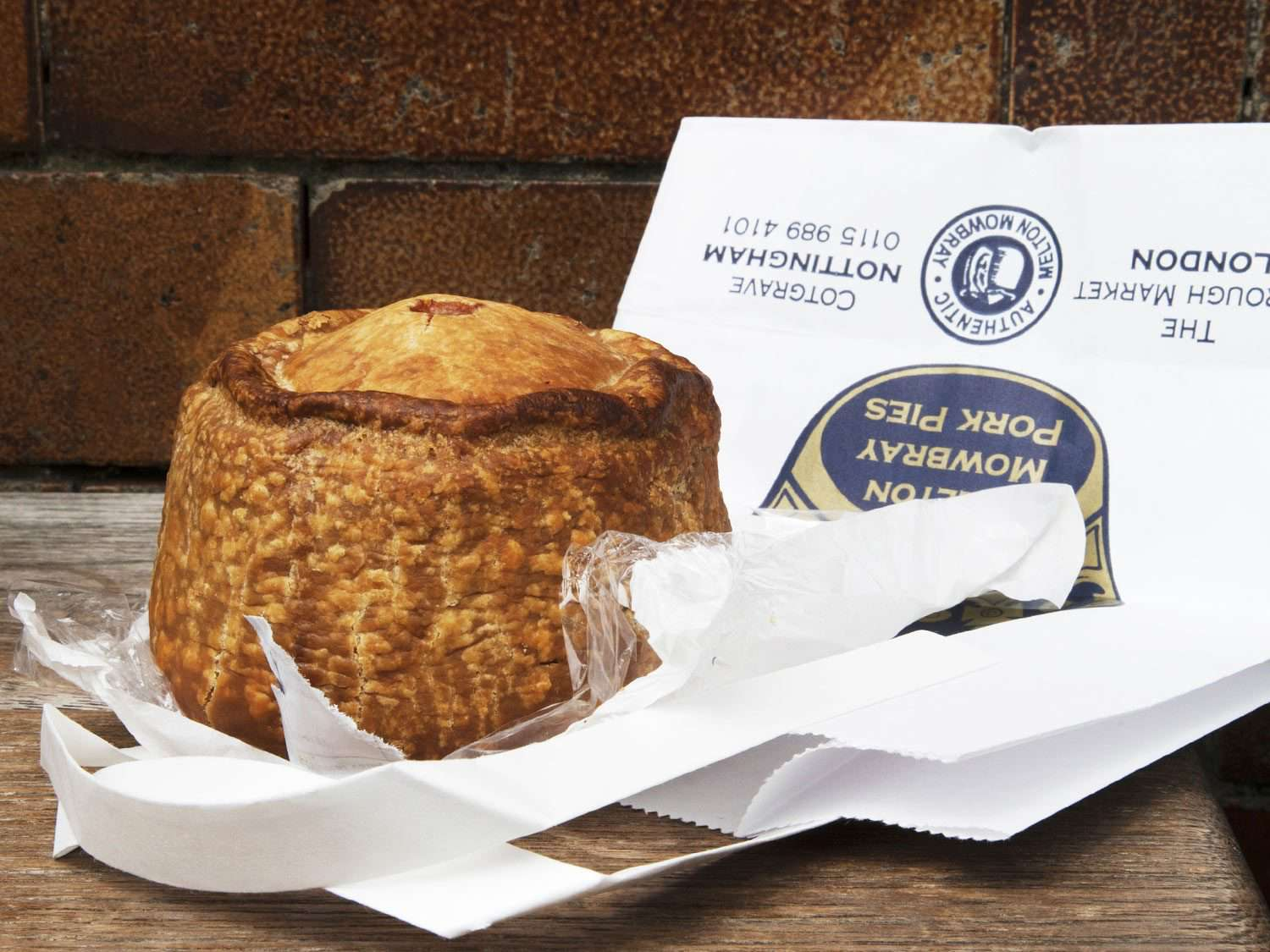 A whole Melton Mowbray pork pie, unwrapped, next to a paper shopping bag from Mrs. King's