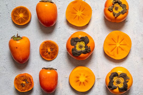 A variety of persimmons, some cut and some whole, arranged in a grid on a stone surface