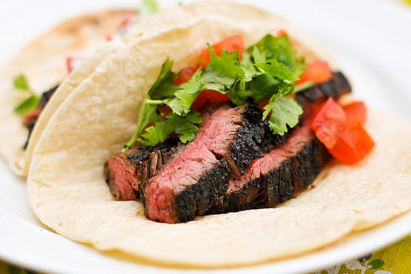 Sliced skirt steak tacos with tomatoes and cilantro on a plate