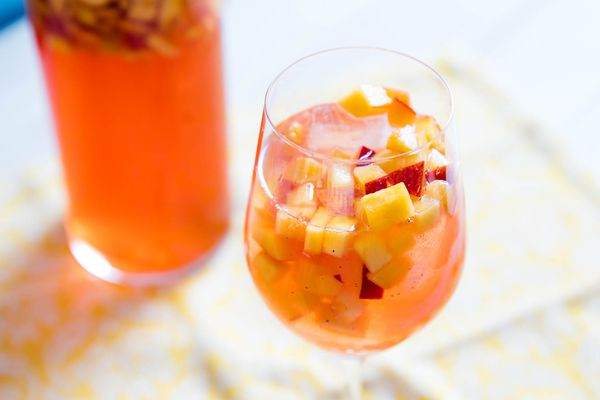 A glass of Sparkling Rosé Sangria With Aperol and Peaches, and a pitcher of the cocktail in the background.
