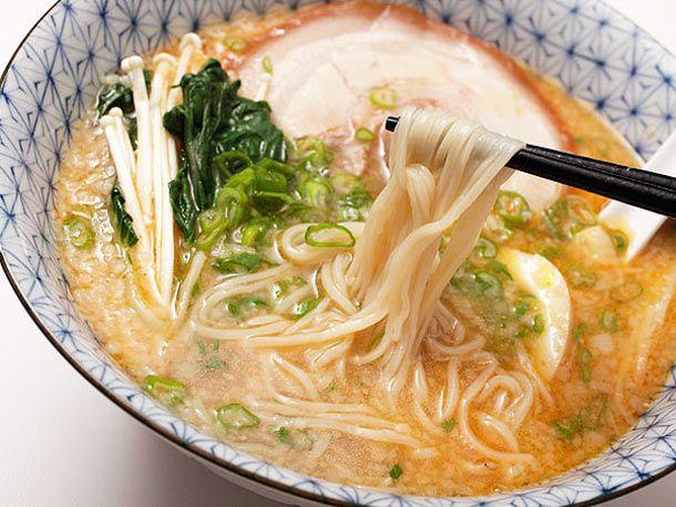 Chopsticks pulling noodles out of bowl of tonkotsu ramen