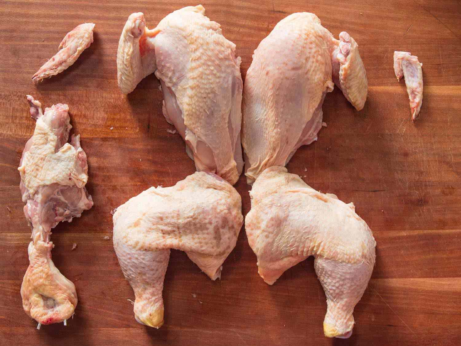 Chicken broken down into four pieces with wing tips and back for stock.
